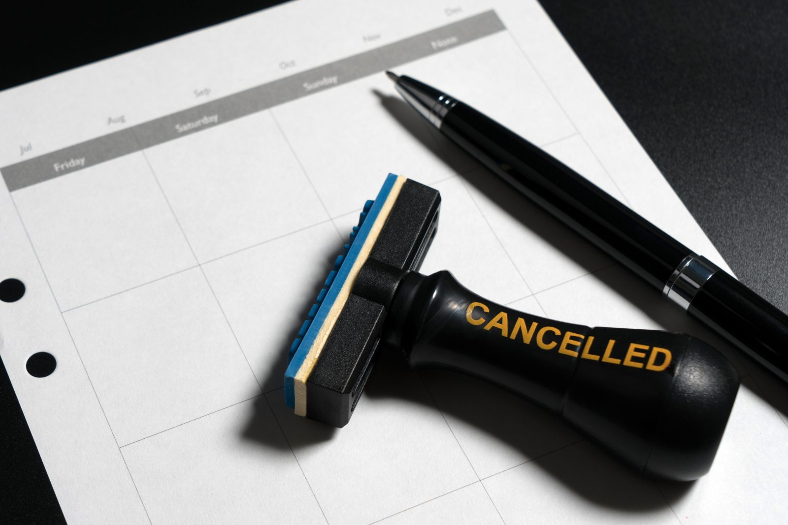 Cancelled planning, appointment, schedule, meeting concept. Business planning cancelled with blank calendar, pen and cancelled rubber stamp on black background.